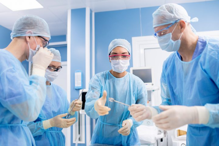 Group of four professionals in protective uniform taking surgical instruments